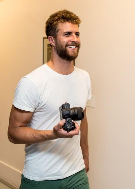 Manu Bruckstein mit einer Filmkamera auf während eines Jobs